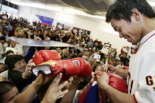 Pacquiao signs autographs for thousands of fans during a free public workout at the Westwind School in Phoenix.