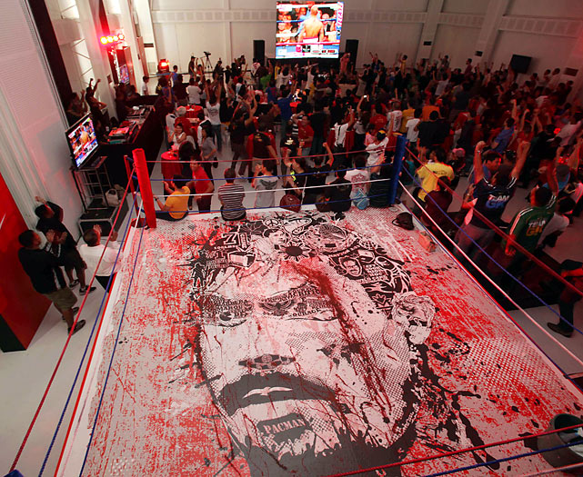 Fans gathered inside a gym that has a mural of Pacquiao in the ring to watch a tv broadcast of his fight against Miguel Cotto.  Pacquiao took the WBO welterweight crown from Cotto by TKO, becoming the first boxer to win titles in seven different weight classes.