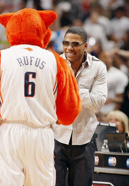 Rapper Nelly shares a cute moment with Bobcats mascot Rufus during a first-round game in Charlotte.
