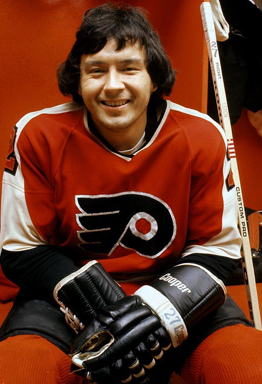 """When facing Philadelphia, it was easy for teams to focus on Bobby Clarke and Bill Barber, but """"The Riverton Rifle"""" often made them pay.  Drafted by Boston third overall in 1970, Leach was traded to the Flyers by the California Golden Seals in '74 and blossomed during Philly's run to a second successive Cup.  Playing on a line with Clarke and Barber, he scored 45 regular season goals and another eight in 17 postseason games. In 1975-76, he tallied 61 and earned the Conn Smythe Trophy by netting 19 in 16 playoff games, even though the Flyers were swept in the Cup final.  He had another 50-goal season in `79-`80 when he helped the Flyers go a record 35 games without a loss and reach the Cup final, where they fell to the Islanders."""