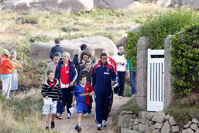 France's national soccer team coach Raymond Domenech and Henry are surrounded by fans on the Sentier des Douaniers path in Perros Guirec, western France.