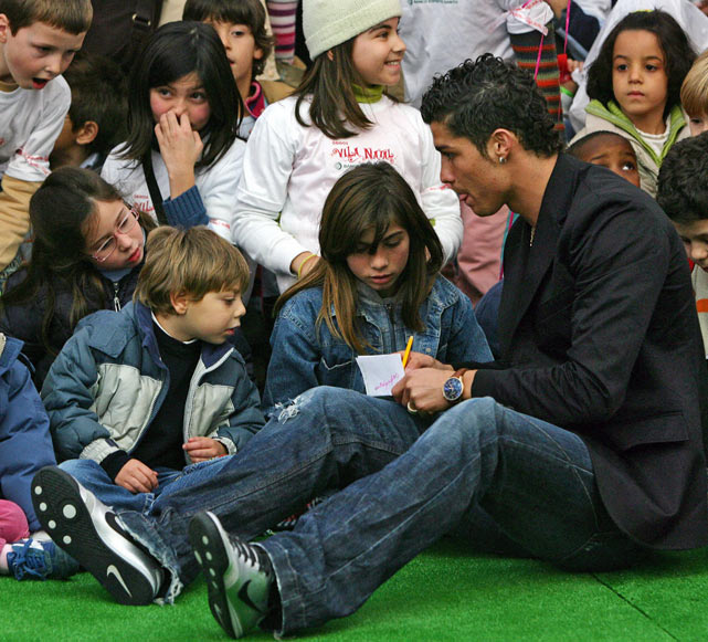 After giving Christmas gifts to a group of underprivileged children, Ronaldo takes time to sign autographs.