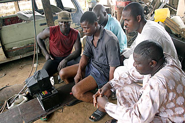 Roadside mechanics and their clients watch on a battery-powered two-inch television on June 10  in Lagos, Nigeria, as their home country took on Argentina during the World Cup in South Africa.
