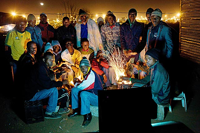 Residents of a squatters' camp in Kliptown, near the Johannesburg township of Soweto, set a small bonfire and watched the World Cup game between South Africa and Uruguay on June 16 on a TV fed with illegally tapped electricity. The home team lost 3-0.
