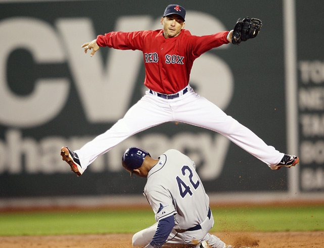 Boston Red Sox shortstop Marco Scutaro leaps to catch a throw as Carl Crawford of the Tampa Bay Rays steals second base during their game on April 16 at Fenway Park in Boston.