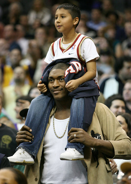 Artest  puts a kid from the crowd on his shoulders as he watches the Lakers-Cavs game at Staples Center.