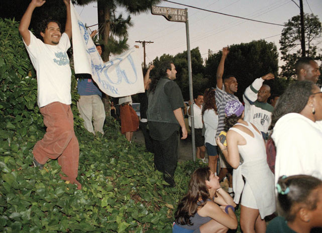 "Simpson fans hold a ""GO O.J."" sign at the intersection of Rockingham Drive and Sunset Boulevard, near Simpson's mansion."