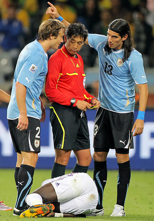 As France's Bakari Sagna lay injured on the ground after a challenge, Uruguay's Nicolas Lodeiro was sent off with a second yellow card. The pleas of teammates Diego Lugano (left) and Sebastian Abreu did not convince the referee otherwise.
