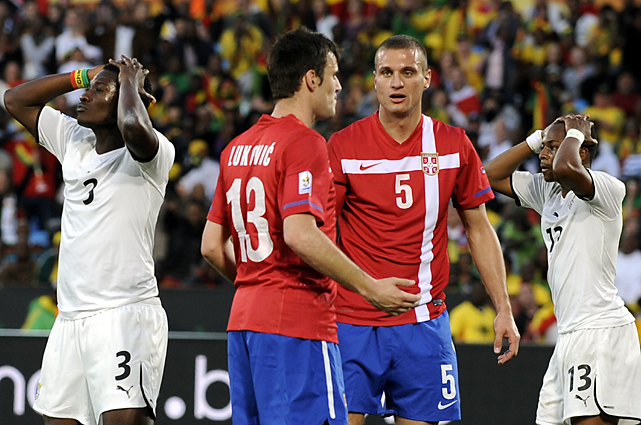 Ghana's Asamoah Gyan (far left) and midfielder Andre Ayew (far right) react to missing a scoring opportunity as Serbia's Aleksandar Lukovic and Nemanja Vidic discuss strategy.