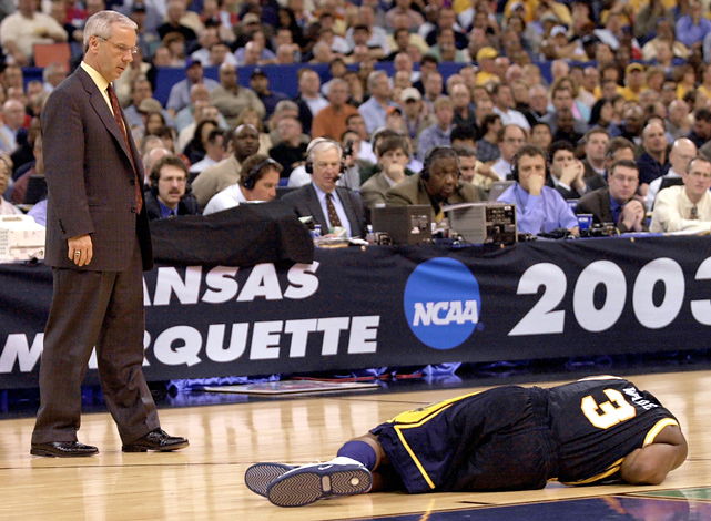 Kansas coach Roy Williams looks down at Marquette's Dwyane Wade, who had gotten hit in the nose, during their Final Four game.  The Jayhawks would go onto win 81-78.