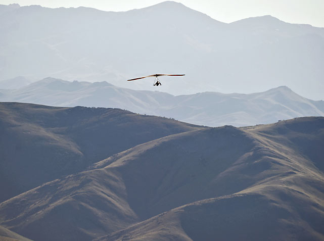 A pilot glides amidst a background of Idaho mountains.