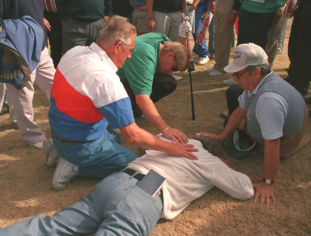 A concerned Daly checks on the condition of a tournament volunteer whom he hit in the back of the head with a tee shot during a tournament in Tucson, Ariz.