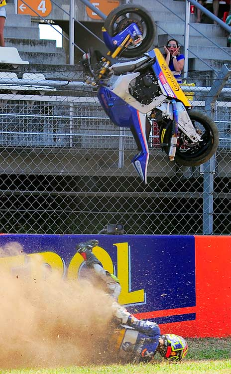 A spectator reacts in the background as Tenerife 40's Carmelo Morales crashes during the Moto2 race of the Catalunya Grand Prix on July 4 in Montmelo, near Barcelona, Spain.