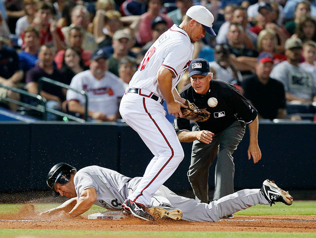 The Marlins' Wes Helms slides safely into third base in the 11th inning as Chipper Jones bobbles the throw during the Braves' 4-3 win July 2 in Atlanta.