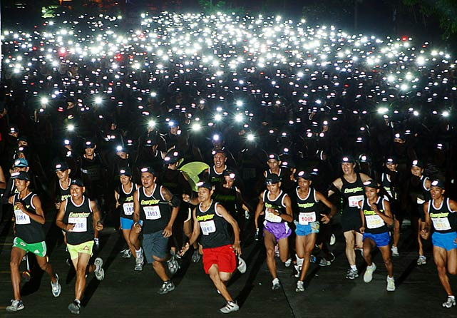 "Thousands of runners use headlights to participate in the ""Energizer night race"" July 10 in Mandaue, Cebu City, Central Philippines. The event was held as part of a run-for-a-cause for the benefit of hearing-impaired children in the province of Cebu."