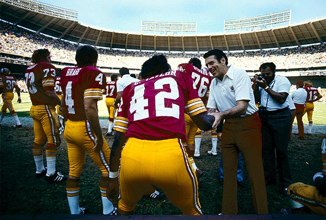 Redskins coach George Allen congratulates wide receiver Charley Taylor, who would go on to finish with 53 receptions and six touchdowns on the season.