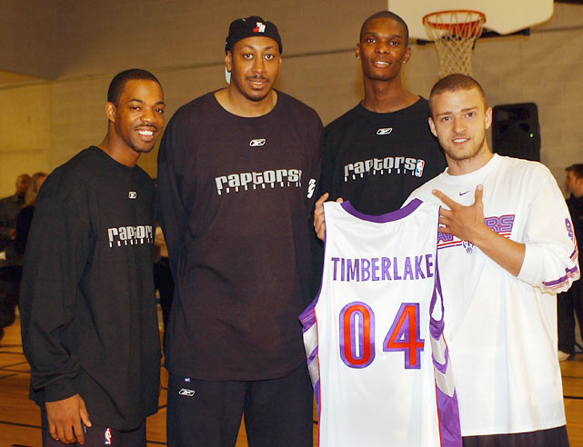 Justin Timberlake holds up a personalized Raptors' jersey as he poses for a photo with Rafer Alston, Donyell Marshall and Bosh while visiting with a group of eighth graders in Toronto.