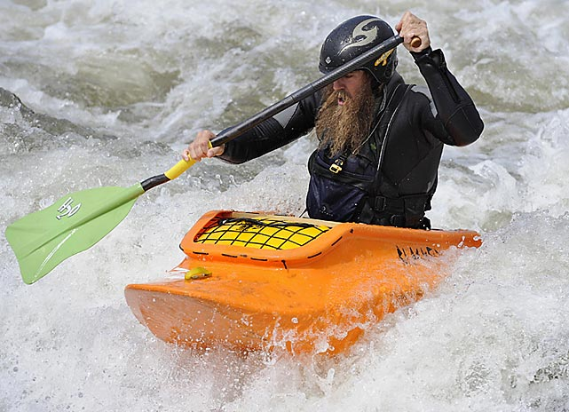 Old man of the river Eli Helbert navigates his open canoe on the wave.