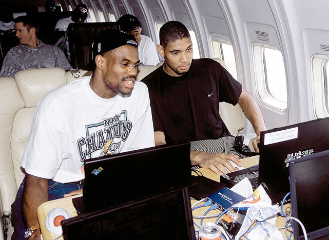 David Robinson and Tim Duncan work on their computers on their flight back to San Antonio after defeating the Knicks to win the 1999 NBA championship.