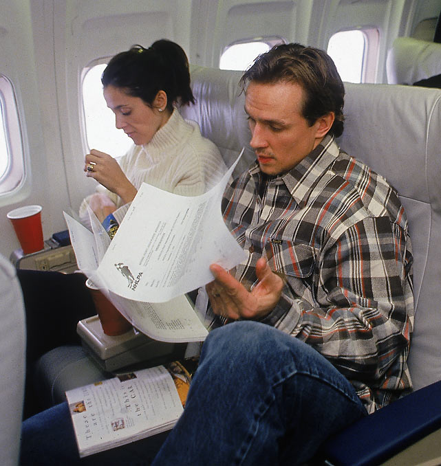 Steve Yzerman sits on an airplane and reads a document on a flight back to Detroit.