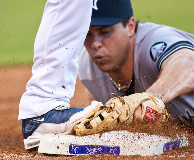 New York Yankees first baseman Mark Teixeira dives to first base in time to beat Kansas City's Mike Aviles for an out in New York's 4-3 road victory on Aug. 12.