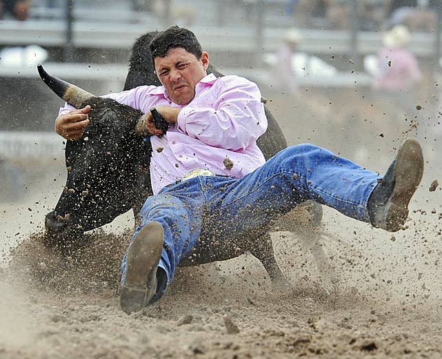 Blaine Jones from Templeton, Calif., locks on during steer wrestling.