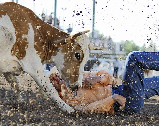 A rider grimaces upon hitting the dirt in the steer-wrestling event.