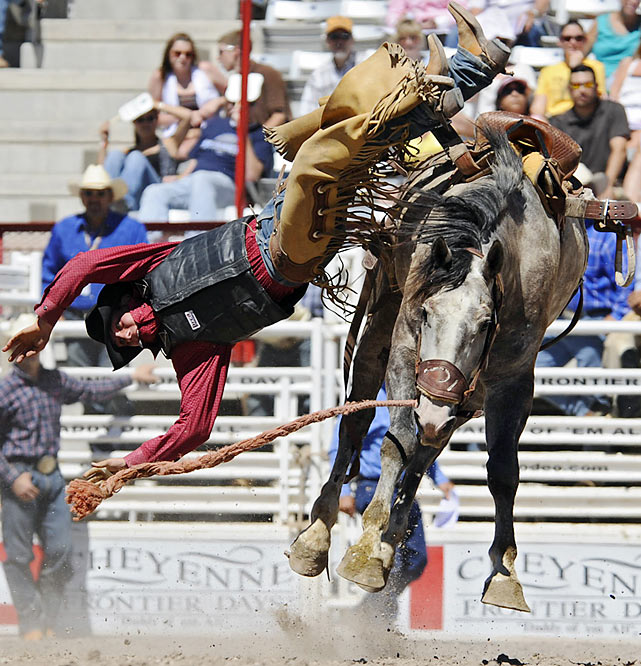 Saddle bronc rider Charlie Kogianes of Provo, Utah, is about to hit the dirt face-first.