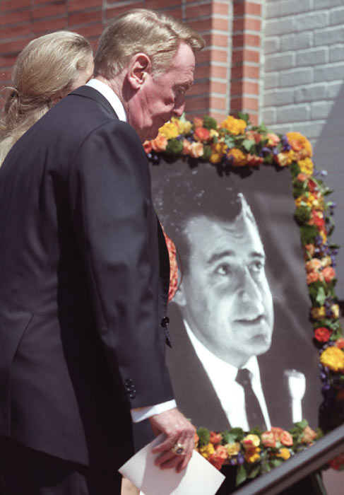 Scully walks past a picture of Lakers announcer Chick Hearn as he enters the church for Hearn's funeral.