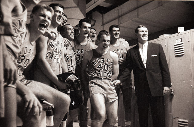 "North Carolina basketball coach Frank McGuire poses with his Tar Heels before the 1956 Dixie Classic. The 1956-57 Tar Heels were dubbed ""McGuire's Miracle"" after they completed a 32-0 season and captured North Carolina's first NCAA championship."