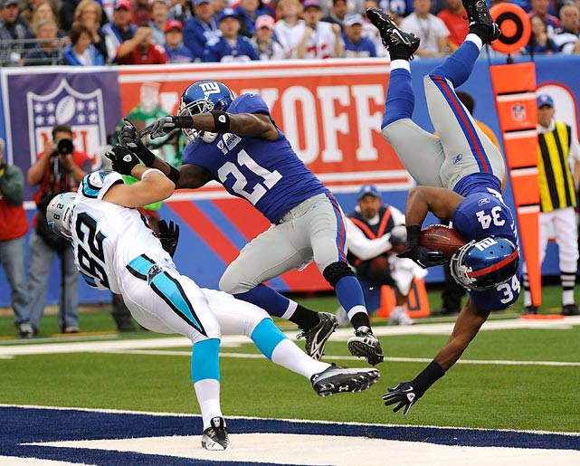 Deon Grant (34) of the New York Giants intercepts a pass intended for Carolina Panthers Gary Barnidge, who also drew the attention of Kenny Phillips (21). The Giants defeated the Panthers 31-18 in the new Meadowlands stadium.