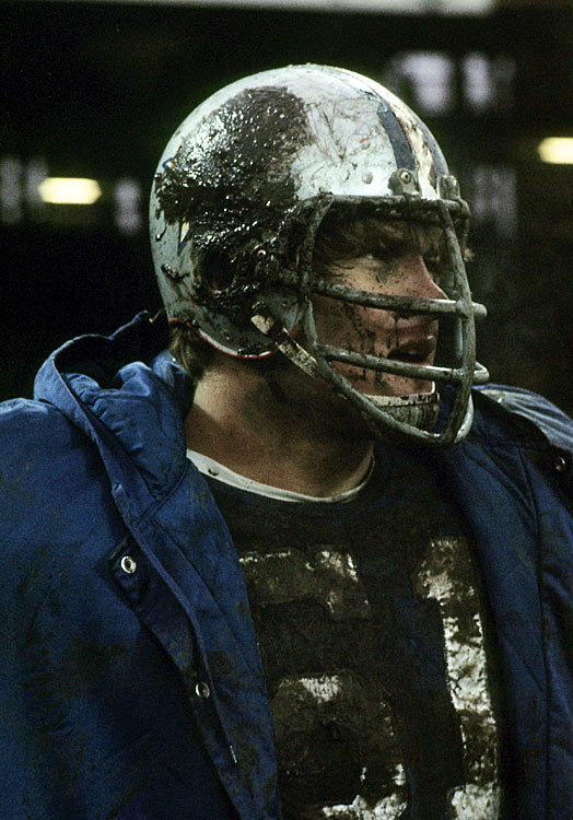 Caked in mud, Dallas Cowboys offensive tackle Blaine Nye peers in at the action. In addition to Nye's on-field ethic, he was driven off the field as well, earning a M.S. in physics from the University of Washington and an M.B.A. from Stanford amid his nine-year NFL career.