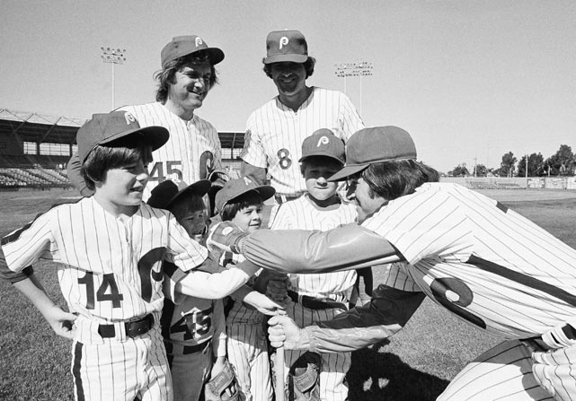 Rose tweaks the chin of six-year-old Mark McGraw as some of the Phillies and their sons got together during a spring training workout at Jack Russell Stadium in Clearwater, Fla. From left are Petey Rose, Mark McGraw, Aaron Boone and Brett Boone. Pitcher Tug McGraw (left) and catcher Bob Boone stand above the group.