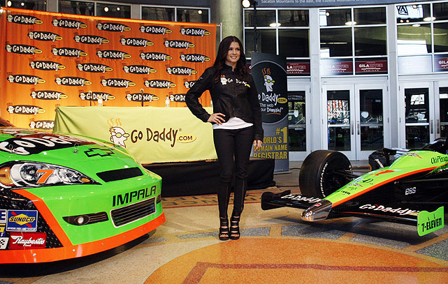 Danica strikes a pose between her two Go Daddy-sponsored rides.