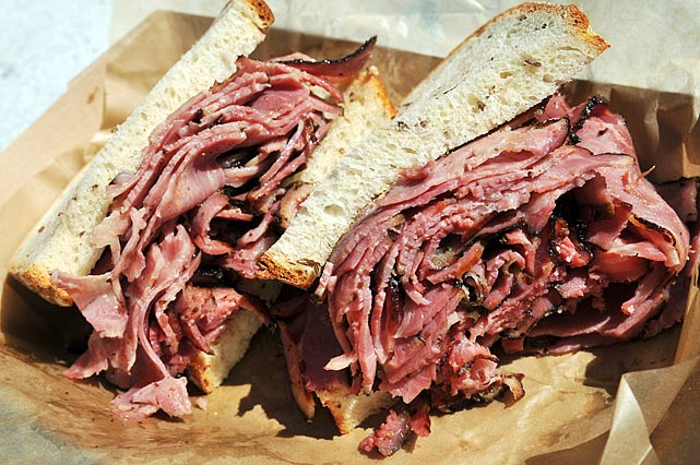 """This looks pretty good. And it's still too big to eat (like the midtown Carnegie deli). [ Tries it. ] Yeah, there's nothing wrong with this. They're using their pastrami. They're one of the few delis that still makes their own pastrami -- not on the premises, they make it in Jersey in a plant -- but still, it tastes really good. This is a better pastrami sandwich than you can get at 90 percent of the delis in New York."""