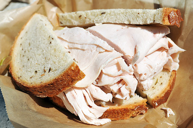 """The double-wide turkey sandwich is a mistake. Turkey's got to be drier. The ratio of this sandwich is all wrong. What I would do is take half the turkey off it. It's actually surprisingly moist. I'm shocked. It doesn't taste bad, it's just way too much turkey. Once you take half the turkey off the sandwich, it's a solid turkey sandwich. If you put the cole slaw on it, it'd probably be a really good turkey sandwich."""