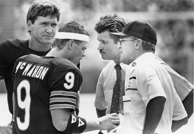 McMahon chats with Ditka, offensive coordinator Ed Hughes and backup QB Steve Fuller during a game against Green Bay. McMahon threw for 2,392 yards, 15 touchdowns and 11 interceptions during the 1985 season.
