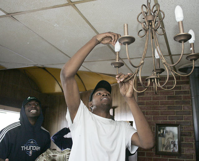 Ever the handyman, Durant fixes a chandelier at an Oklahoma City resident's home in April 2009.  At 6-foot-9, Durant didn't need a ladder, something that clearly was amusing to teammate Jeff Green (back).