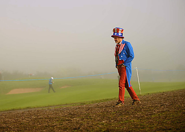 A dejected fan of the U.S. Ryder Cup team walks through the fog and mud at the Celtic Manor Golf Club in Newport, Wales. The European team defeated the U.S. 14 1/2 to 13 1/2.
