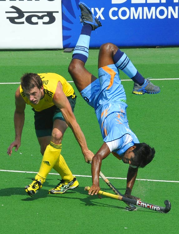Simon Orchard of Australia fights for the ball with Prabodh Tirkey of India in the field hockey final of the XIX Commonwealth Games at the Major Dhyan Chand National Stadium in New Delhi on Oct. 14.  Australia won the gold by beating India 8-0 in the final.