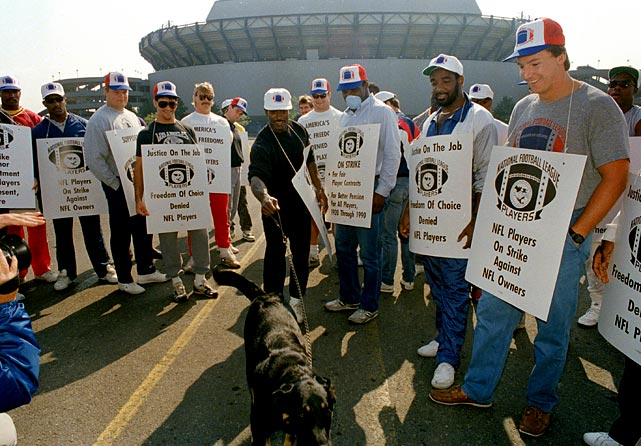 Amid the 1987 players' strike, Giants' safety Kenny Hill pretends to unleash his dog on a nearby group of photographers.  The players' voted to strike on Sept. 22, a protest that would continue for 24 days.  That lost time would be quite costly for Hill and Co., as the Giants' replacements lost all three contests they participated in, and New York failed to make the playoffs to defend its 1986 Super Bowl title.