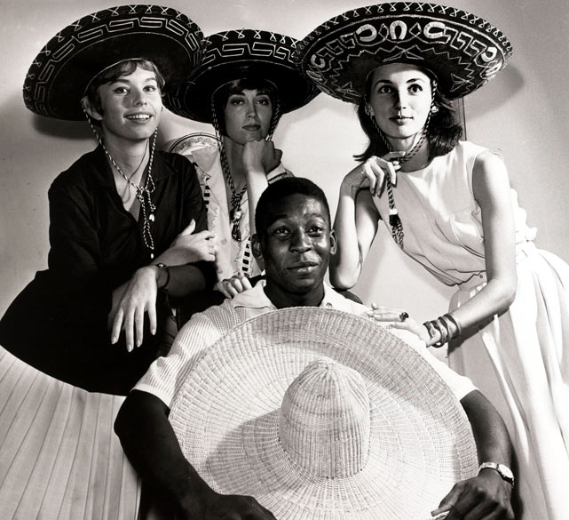 Some female admirers join Pele in his sombrero photo shoot.  He had millions of fans, and is still regarded as a Brazilian national hero.