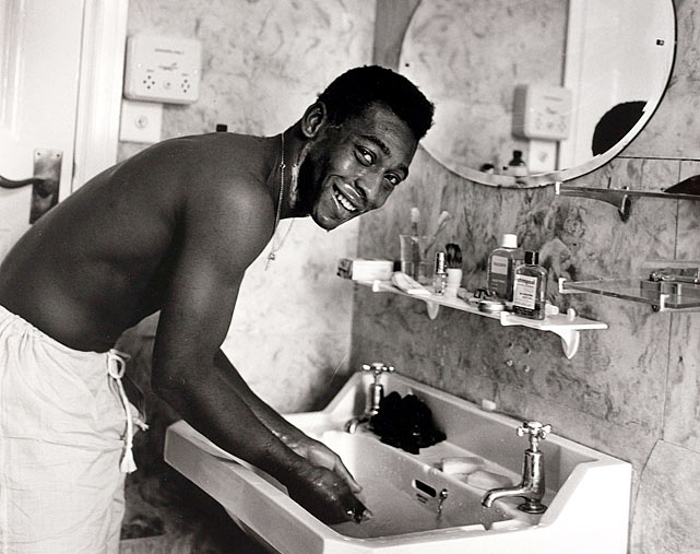 Pele is pictured washing in the bathroom.  He was a media target everywhere he went, becoming the most legendary footballer ever.