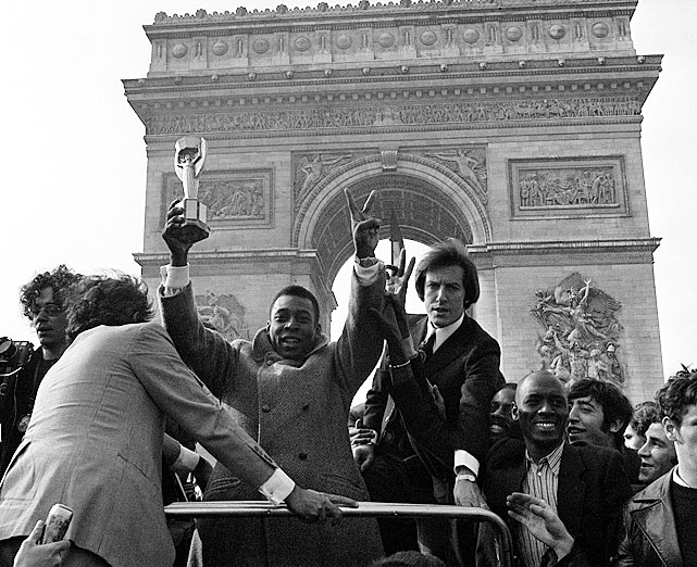 Pele is paraded down the Champs Elysees boasting the Jules Rimet World Cup Trophy, which Brazil was awarded for their dominance in the 1970 tournament.  He was in Paris with his Santos team for a 1971 charity match.