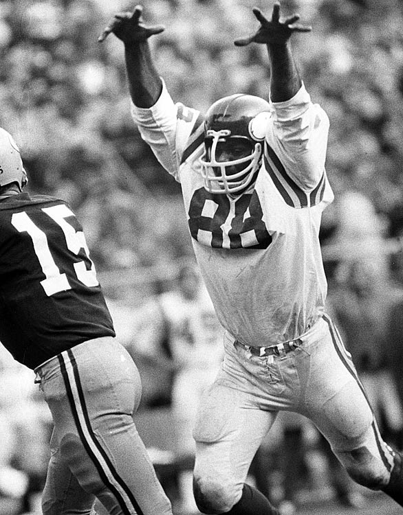 Hall of Fame defensive end Alan Page launches himself at Bart Starr during a game at Lambeau Field.