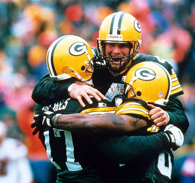 Brett Favre rejoices with teammates John Michels and Andre Rison amid a 1997 NFC Playoff win against the 49ers.