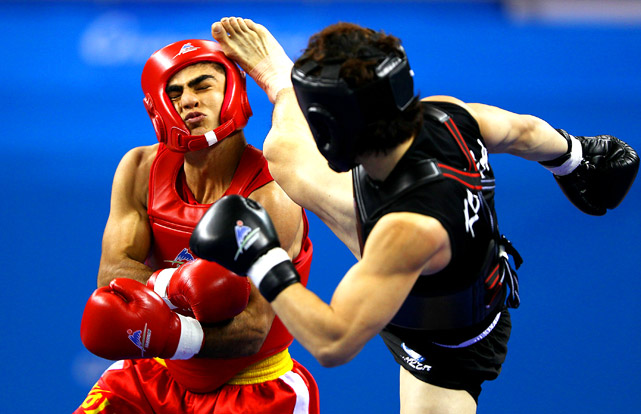 Moshen Mohammadseifi of Iran receives a kick to the head from Jun Yul Kim of South Korea in the 60kg Sanshou Final during the 16th Asian Games at Nansha Gymnasium on November 17 in Guangzhou, China. Mohammadseifi won the gold.
