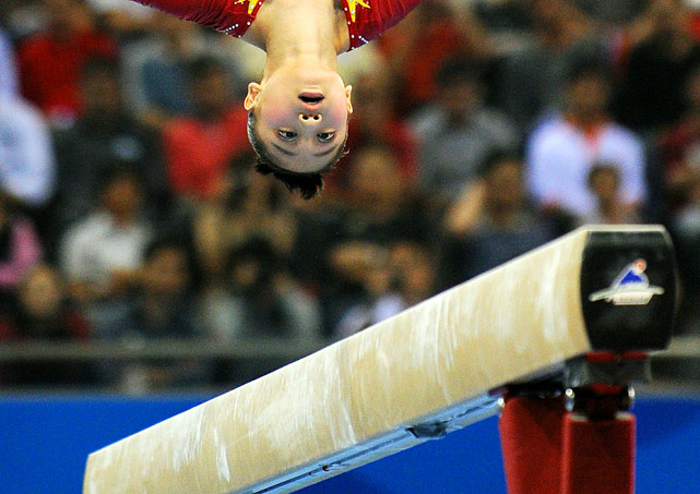Sui Lu of China performs on uneven bars in the individual all-around gymnastics final at the 16th Asian Games. China maintained its 100 percent winning record in the category when Sui won the gold medal.