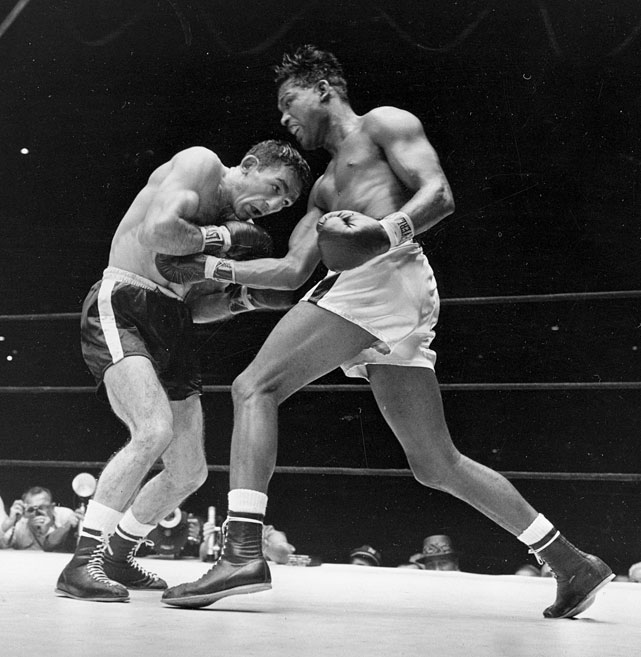 Robinson ( right ) regained the middleweight title a record fifth time with a split-decision victory over Carmen Basilio before 38,000 fans at Yankee Stadium.