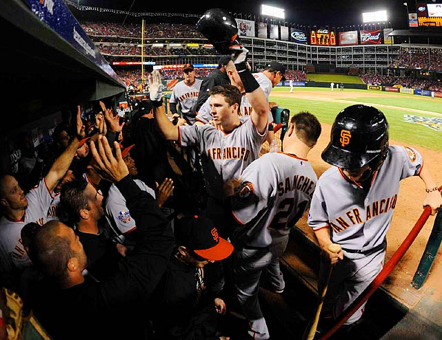 Buster Posey celebrates in the dugout after hitting a home run in the Giants' Game 4 win.  The team did plenty of high-fiving:  outscoring the Rangers 29-12 in the five-game set.